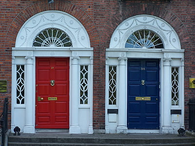 two red and blue wooden door close near gray concrete pavement at daytime