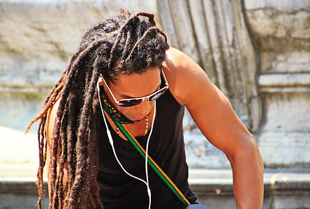 man in black tank top using white earphones