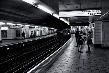 Monochrome shot of subway passengers as they wait for their train on the London Underground