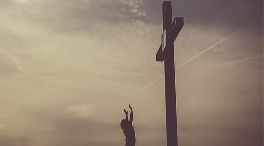silhouette photography of person standing in front of cross