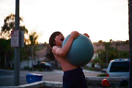 boy holding blue fitness ball