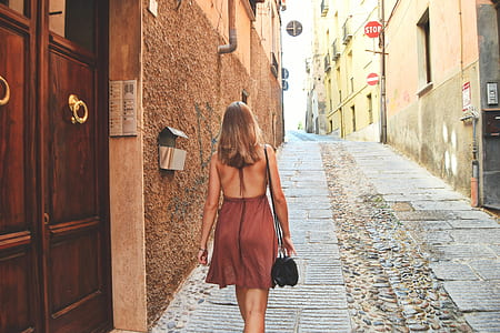 woman wearing brown backless dress walking near brown concrete building during daytime