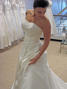 woman wearing white tube wedding gown near white gowns