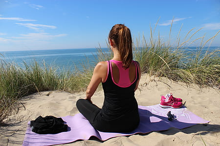 woman in black sleeveless top and black leggings sitting of purple yoga mat on sand near body of water during daytime