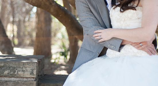 man in gray suit hugging woman in white dress