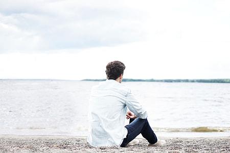 man in white dress shirt and black denim jeans sitting on sand watching seawave during daytime