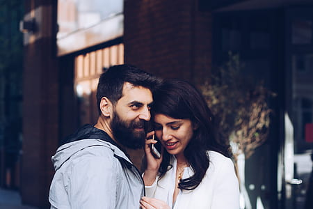 man in gray jacket beside woman with taking call with smartphone