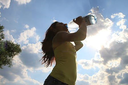 woman in yellow sleeveless top drinking water during daytime