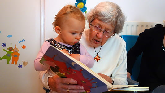 woman wearing white sweater holding book with girl in purple long-sleeved shirt