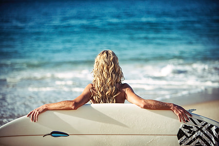 Woman on summer beach with surfboard