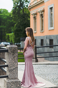 woman wearing pink satin sweep evening gown standing near metal barricade during daytime