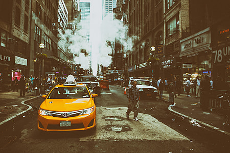 Street shot containing a yellow taxi cab on an overcast day in Midtown Manhattan in New York City