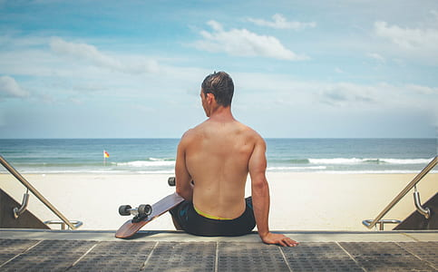 man sitting on staircase holding brown cruiser board near beach during daytime