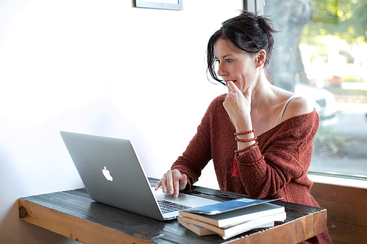 woman touching chin while scrolling through the laptop