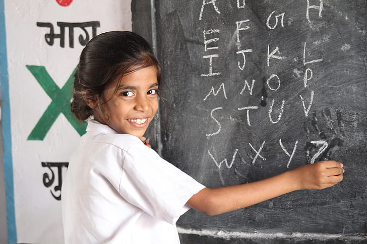 girl holding chalk while writing alphabet on board