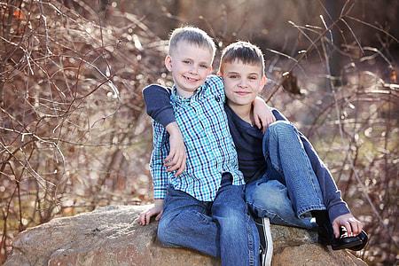 two boy dressed sitting on a big rock