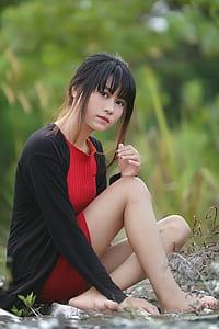 woman sitting on water wearing blac cardigan