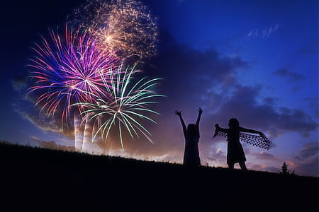 photography of silhoutte of two persons watching fireworks