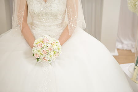 woman wearing white wedding gown holding flower