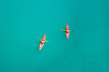 two person riding on red kayak with paddles
