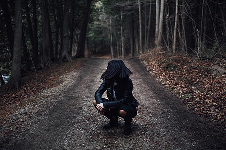 woman in black leather jacket siting on dirt road between trees during daytime