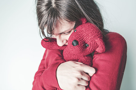 person wearing red sweat shirt and hugging bear plush toy