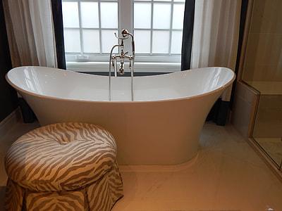 white ceramic tub beside the window