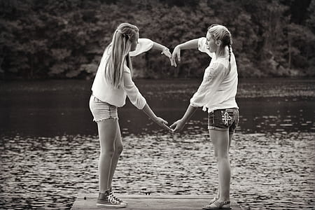 grayscale photo of two woman doing heart sign
