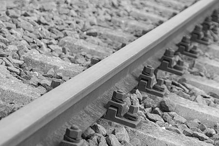 Black Metal Bolts in Silver Metal Train Rail Track Surrounder by Gray Stones