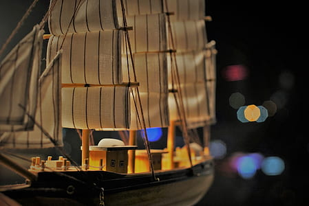 closeup photo of brown and black wood ship model with bokeh background