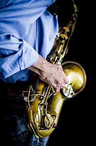 person wearing blue dress shirt playing brass saxophone
