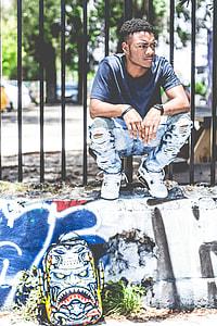 man in black crew-neck t-shirt crouching beside black metal fence during daytime