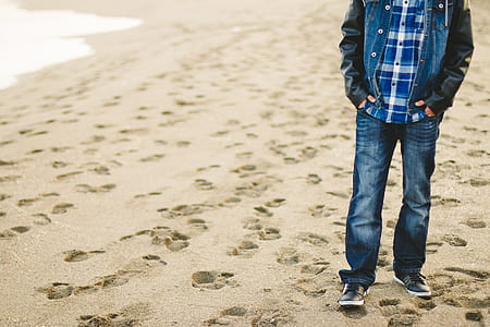 man wearing faded jeans standing on sand
