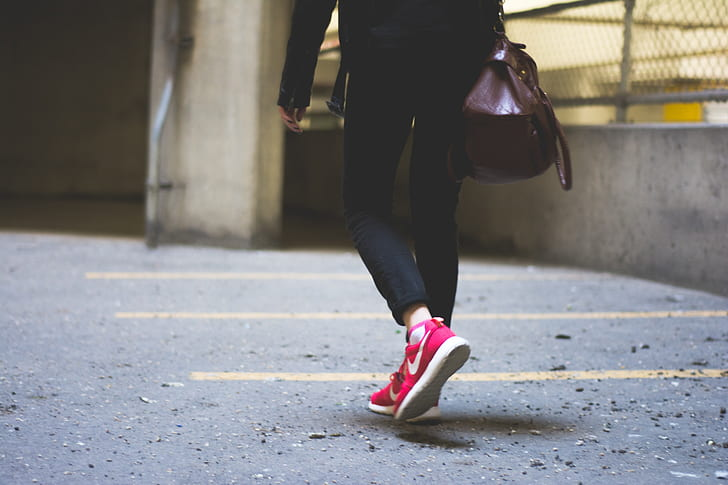 person wearing pink Nike running shoes