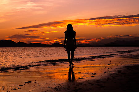 silhouette photograph of woman standing near sea shore
