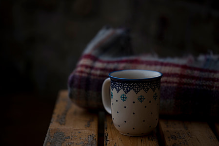 white and blue ceramic mug in front of beige and red textile
