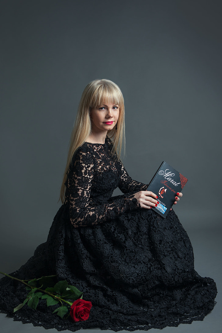 woman wearing black lace dress holding book looking on camera