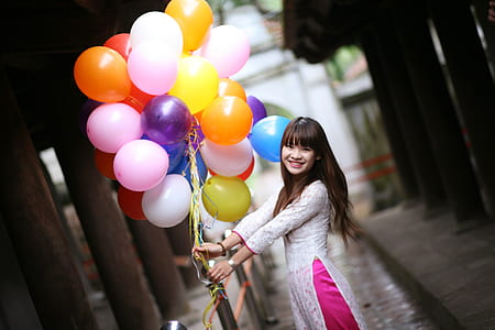 woman in white dress holding assorted-color bundle of balloons