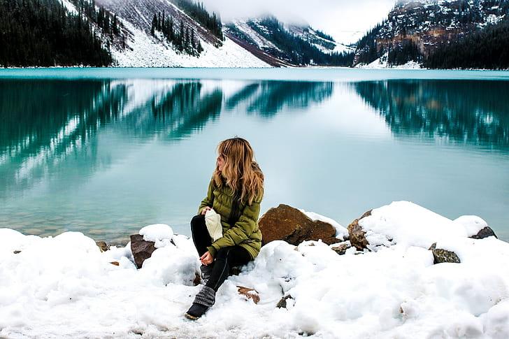 woman sitting on snow near lake