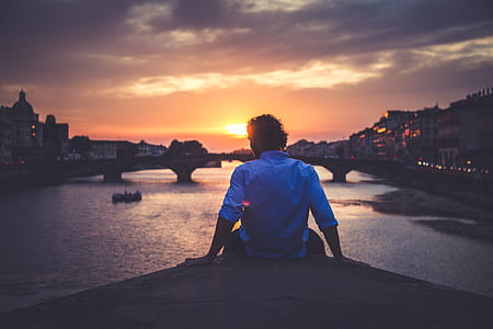 silhouette of man sitting front of bridge during golden hour