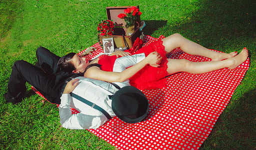 man and woman leaning on red and white plaid picnic mat