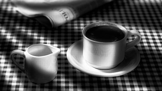 grayscale photography of teacup with saucer beside pitcher