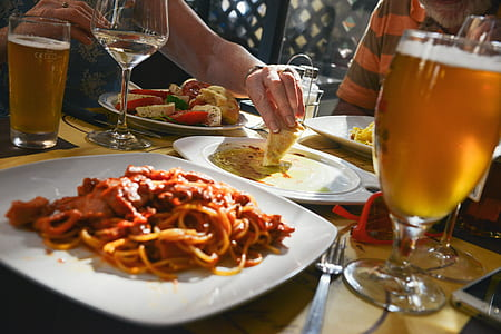 spaghetti on square white ceramic plate beside stainless steel fork