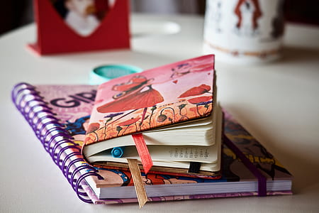 shallow focus photography of two books on white wooden desk