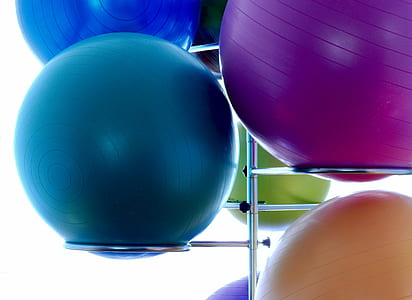 two blue, one purple, and one orange stability balls on stainless steel rack