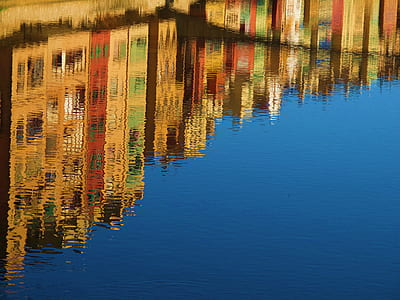 Reflection of High Rise Buildings of Calm Body of Water during Daytime