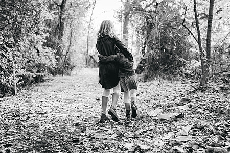 two girls walking on leaf-covered road in forest