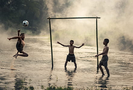three boys playing soccer