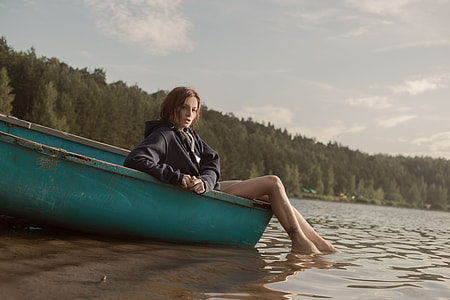 woman in black jacket sitting on green boat near trees during daytime