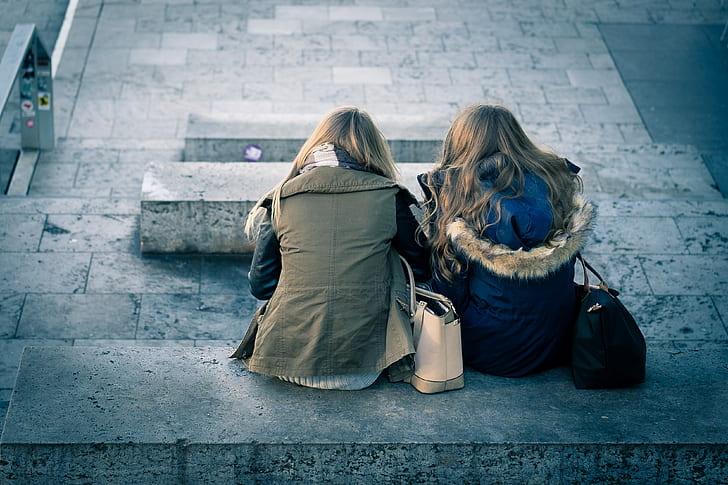 two women sitting on gray concrete bench